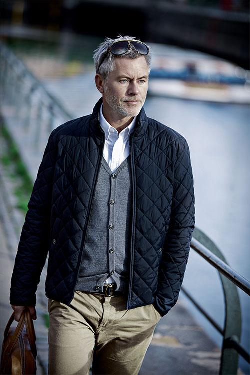 Schwarze Daunenjacke mit Karosteppung, graue Strickweste, weißes Oxfordhemd, beige Chino-Hose