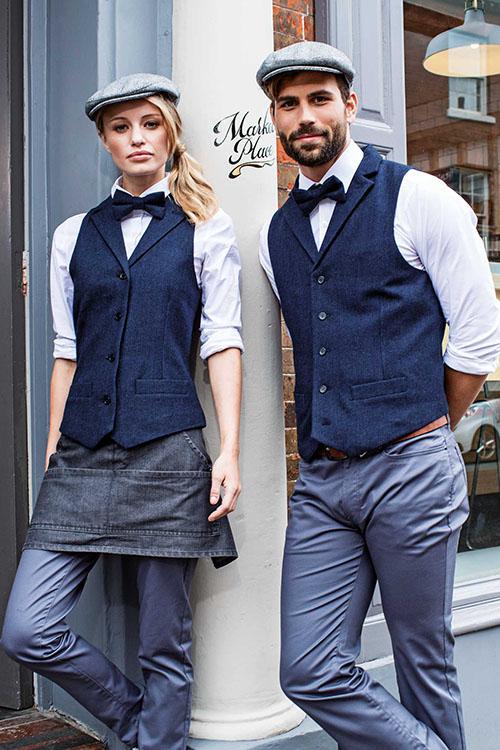 Dunkelblaue Herringbone Weste, weiße Bluse und Hemd, blaue Fliege und Gatsby-Cap. Dazu hellgraue Chino-Hosen und graue Denimvorbinder