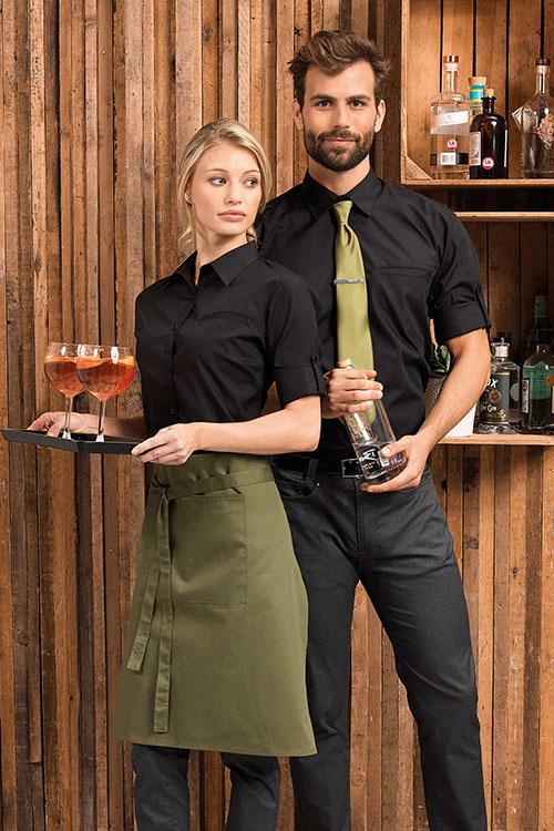 Gastro-Serviceoutfit mit schwarzen Hemden und Blusen und olive-farbenen Schürzen und Krawatten. Dazu graue Chino-Hosen