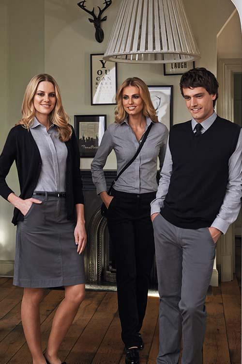 Messebekleidung graue und schwarze Chinohosen, graue Hemden und Blusen, schwarze Strickjacke und Pullunder