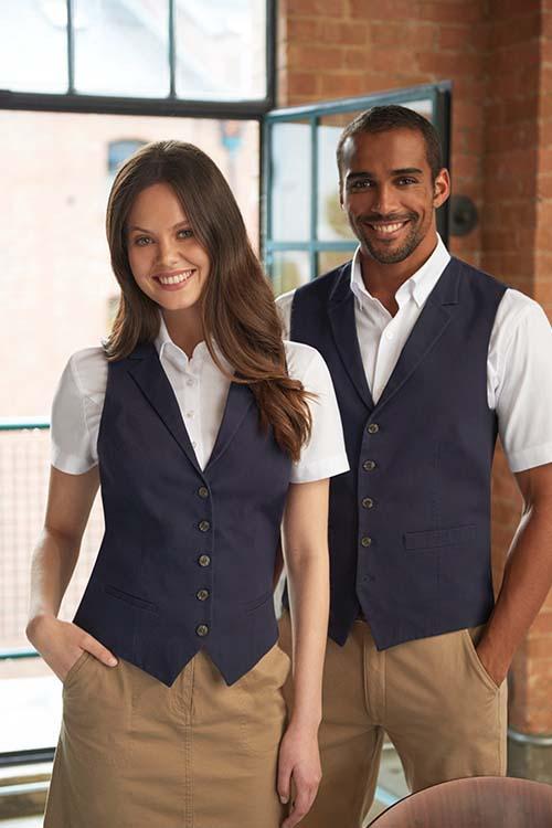 Hotelbekleidung Rezeption blaue Chino Westen, beigefarbene Chino Hosen, weiße Hemden und Blusen