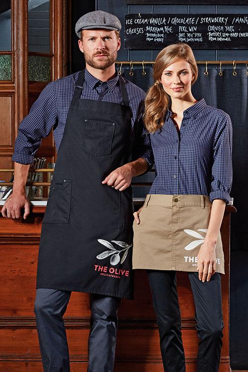 Berufsbekleidung Gastronomie schwarz-blau-karierte Hemden und Blusen, schwarze Latzschürze, beiger Vorbinder, Chino-Hosen